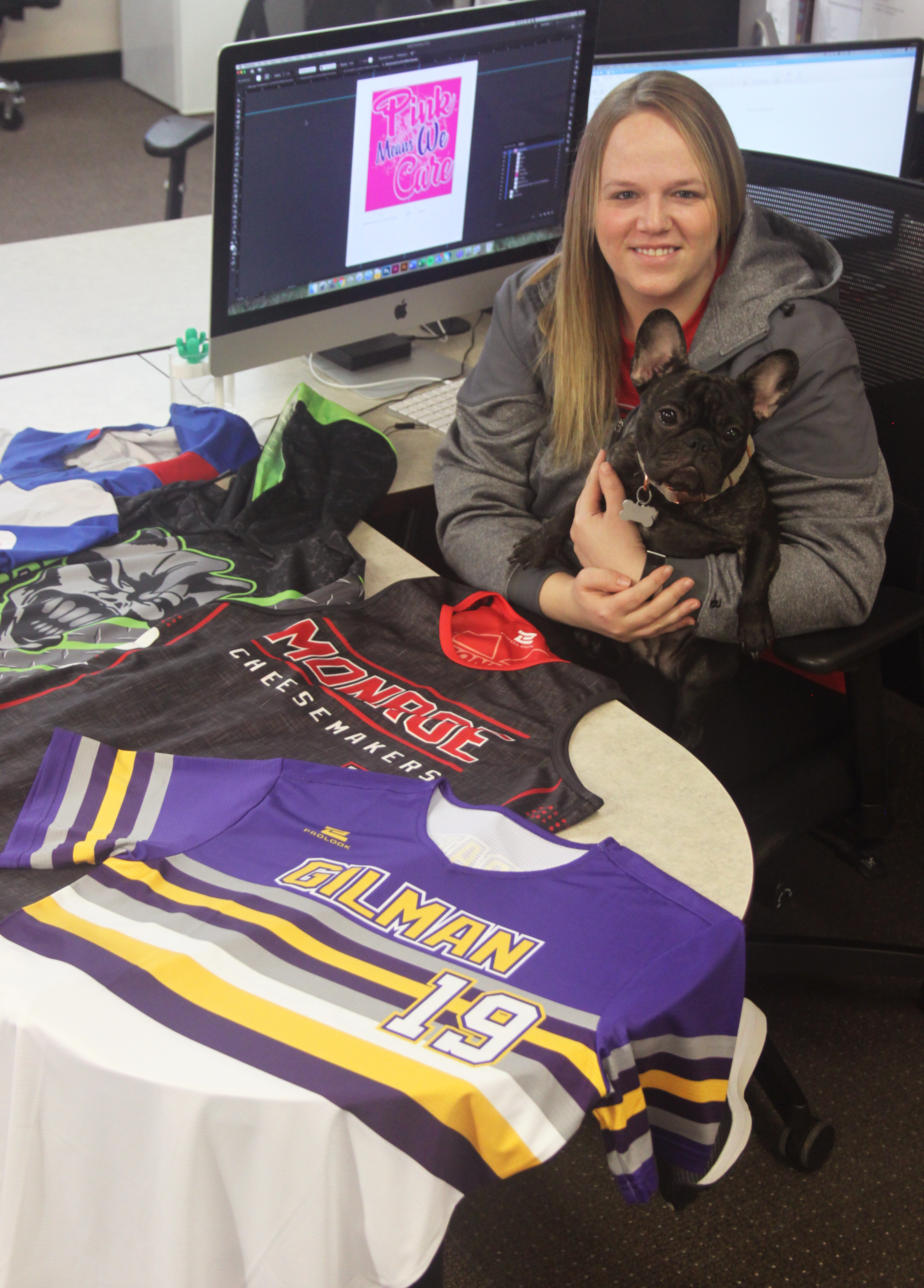 Courtney sitting at her desk holding RBS' french bulldog Bailey by her sublimation designs
